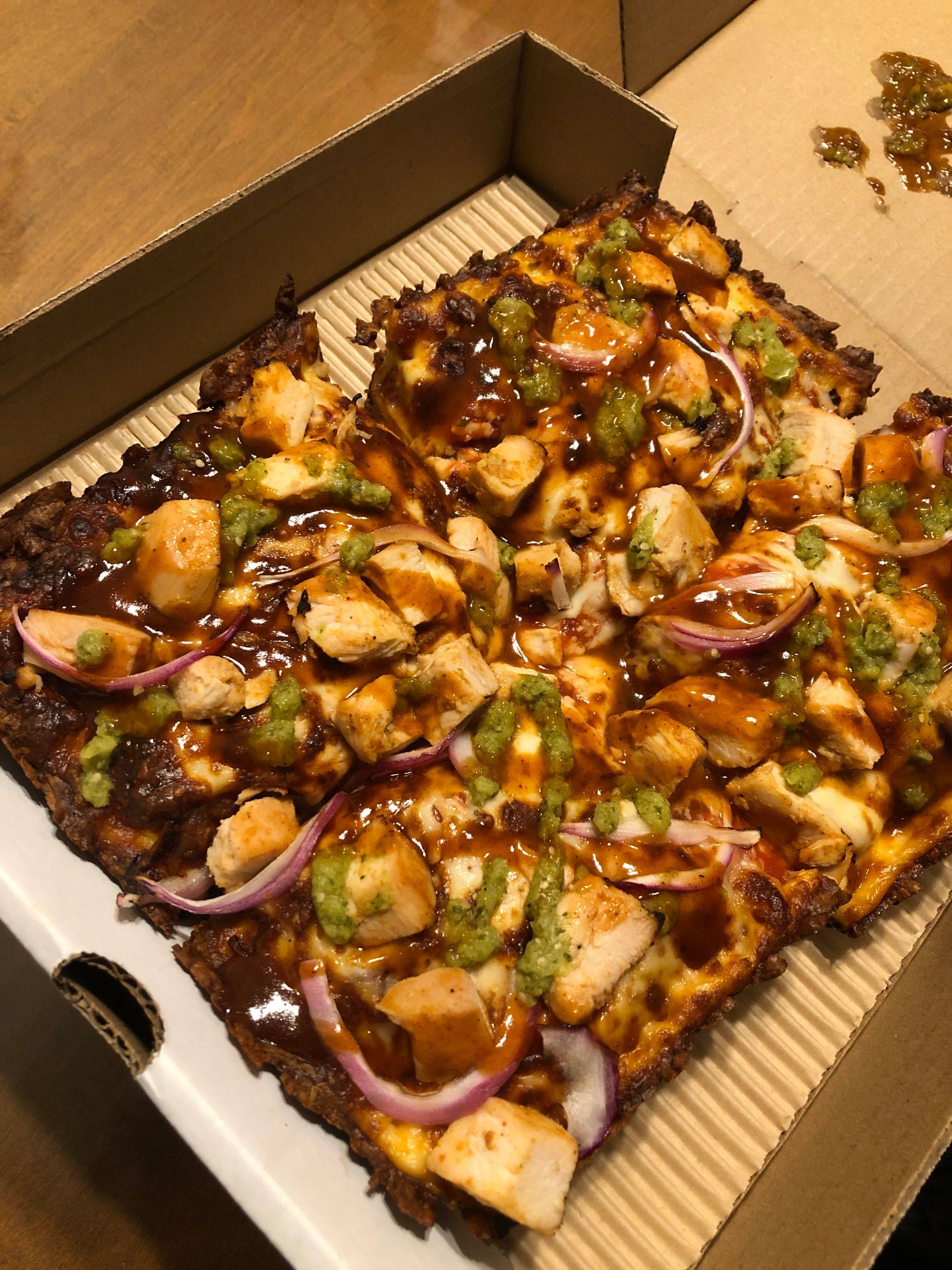 A Detroit-style pizza: square, in a cardboard box, covered in chunks of chicken, bbq sauce, salsa verde and red onions.