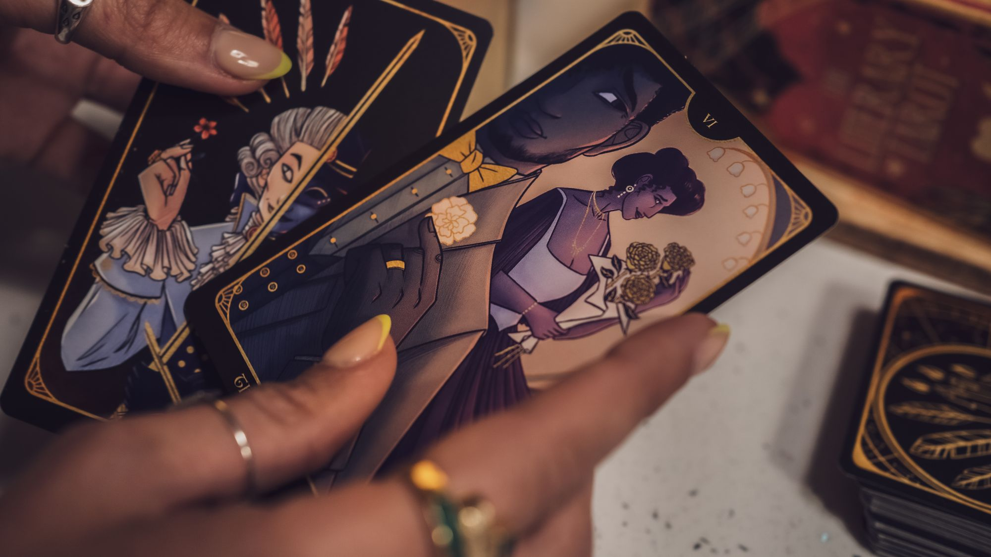 A pair of dark-skinned and well-manicured hands wearing rings hold two illustrated Tarot cards face up from the deck, against a blurred background of stacked, face-down cards showing off the lovely gold-on-black backs. In one face-up card (The Lovers), a Black man in a handsome waistcoat and jacket looks hopefully over his shoulder at an elegant Black woman holding a bouquet of three golden roses.