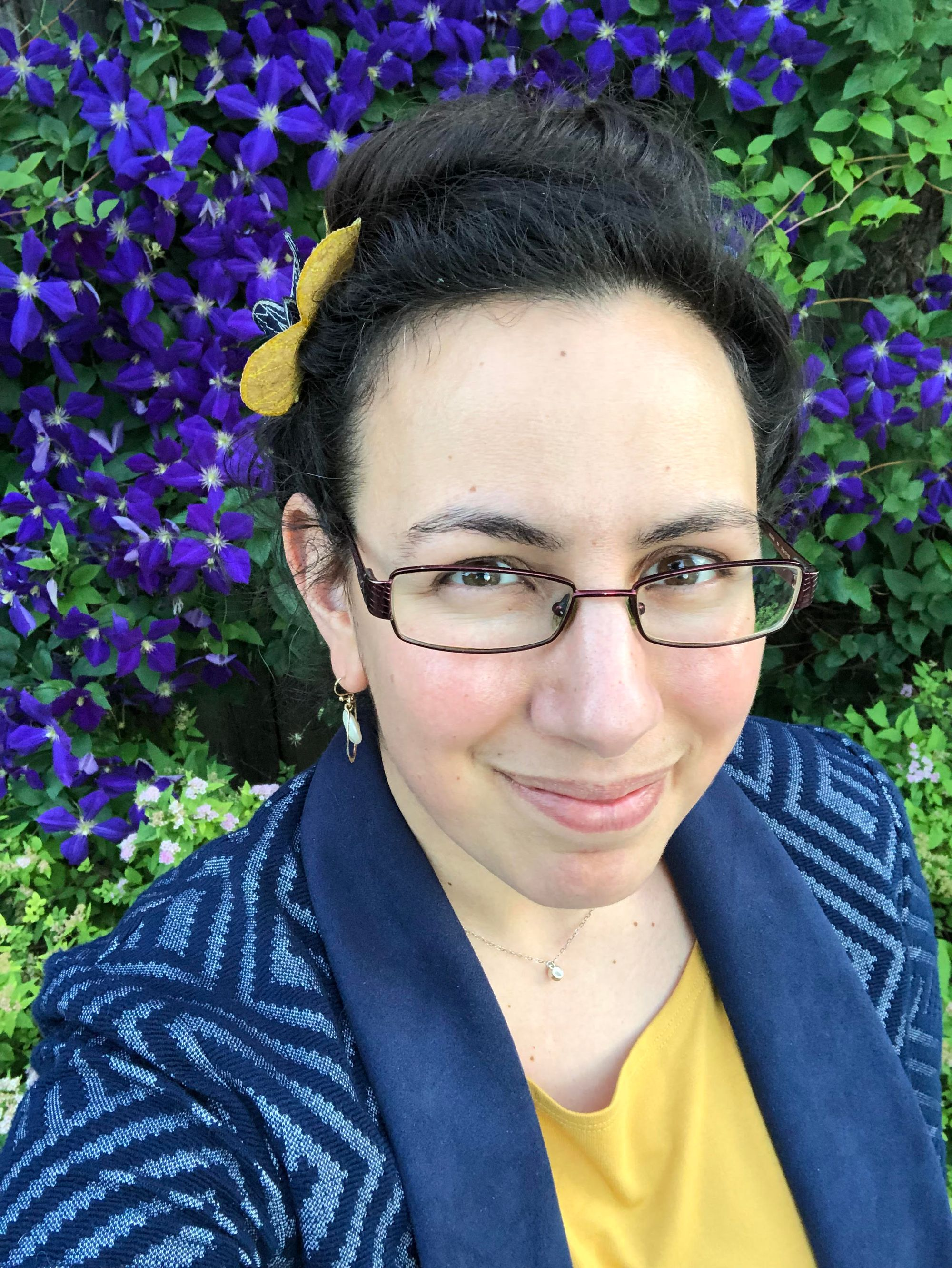 Selfie: I'm wearing glasses and a blue blazer with a geometric pattern over a bright yellow t-shirt against a backdrop of spectacularly purple-blue clematis flowers. I have two silk flowers in my pinned-up dark hair: one bright yellow and one dark blue. I'm wearing a tiny pearl necklace on a short delicate chain and larger freshwater-pearl earrings in a rose-gold setting.