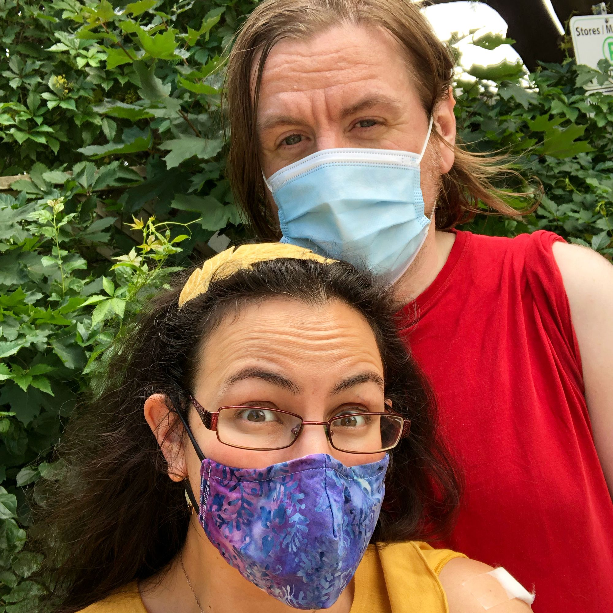Selfie of me and my husband against a background of green foliage. I'm in the foreground, wearing a bright yellow shirt and yellow headband shaped like an oak leaf in my dark brown hair, with glasses and a purple gradient handmade mask on; Stu is a head taller than me, with shoulder-length light brown hair, and wearing a red shirt and a pale blue surgical mask. We both have our left sleeves rolled up to show off our band-aids.