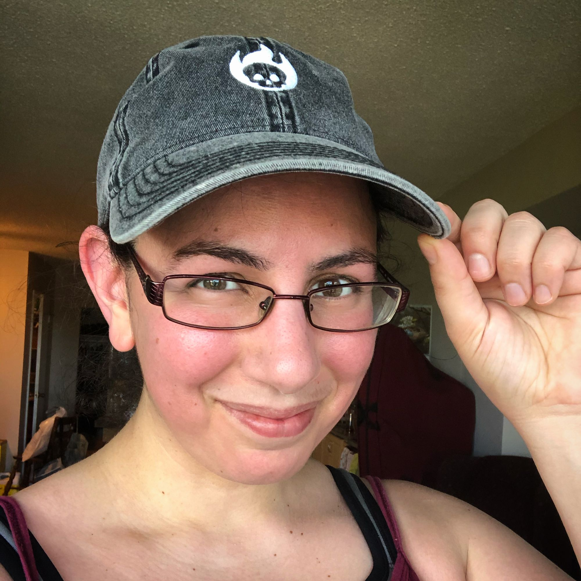 Selfie: close up on my sweaty pink post-run face while wearing a grey denim blaseball cap, featuring a stylized logo of a white embroidered skull engulfed in flame. I'm touching the brim of the cat with two fingers in a kind of salute to show off the merch.