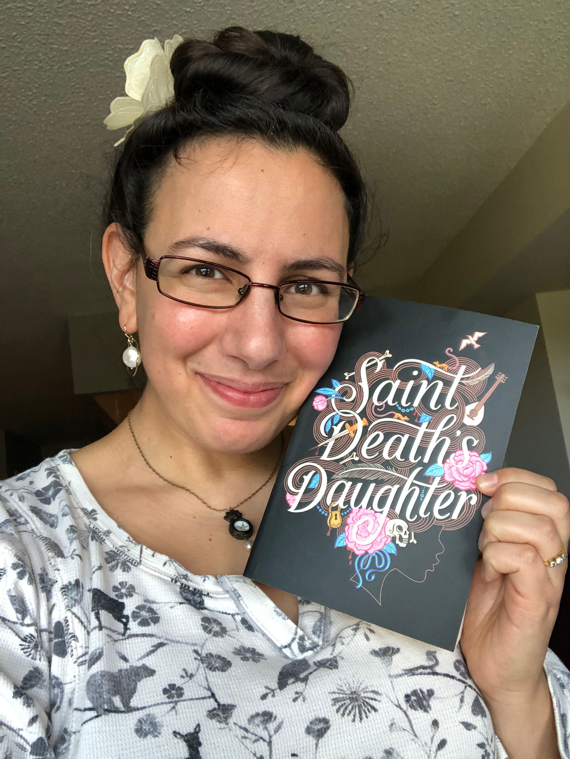 A selfie in which I tenderly rest my cheek against an advanced reading copy of C. S. E. Cooney's SAINT DEATH'S DAUGHTER while looking at the camera. Cover description: against a black background, the title words are in a cursive italic script embellished with pink roses, blue foliage, a dagger, bones, musical instruments, a padlock and a bird in flight. These design elements make up the tangled brown hair of a young woman's profile outlined in brown against the black.